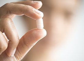 Hand holding a tablet pill